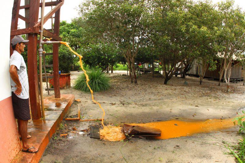 Ribeirinhos realizaram a lavagem de uma das caixas d'água do microssistema implantado pela mineradora. Esgotada a água, procederam à limpeza da caixa – a cor da água que sai nesse processo é semelhante à da bauxita